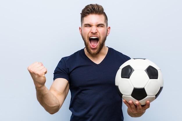 Junger kaukasischer mann, der einen fußball zujubelt sorglos und aufgeregt hält.