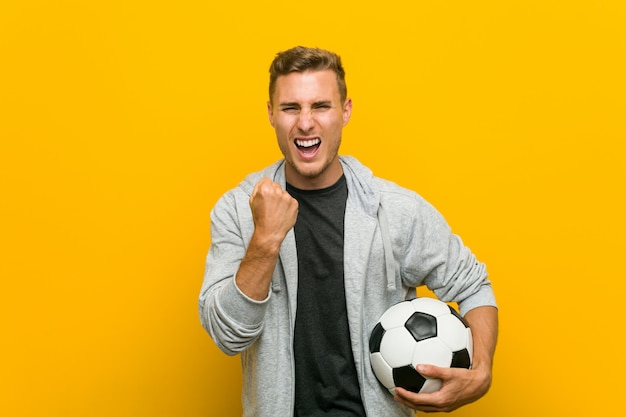 Junger kaukasischer mann, der einen fußball zujubelt sorglos und aufgeregt hält
