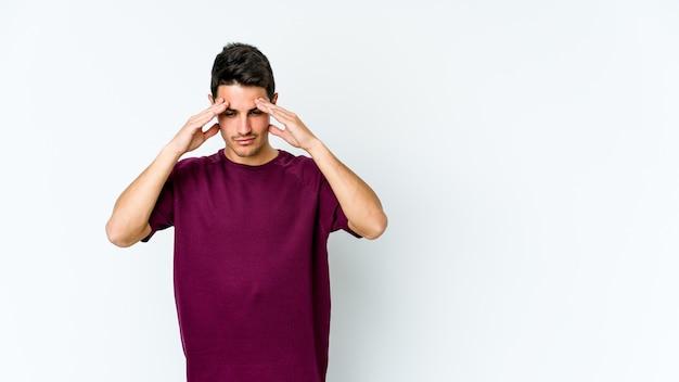 Junger kaukasischer mann, der einen kopfschmerz hat, der vorderseite des gesichts berührt.
