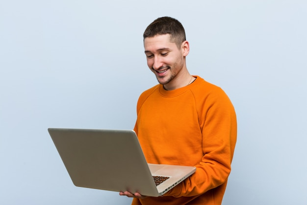 Junger kaukasischer mann, der einen laptop glücklich, lächelnd und nett hält.