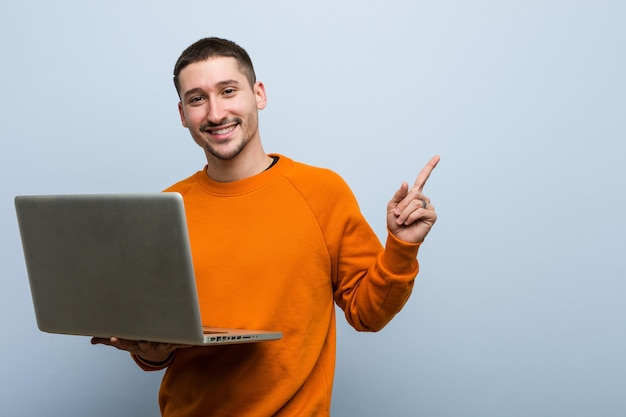 Junger kaukasischer mann, der einen laptop hält, der fröhlich mit zeigefinger weg zeigt.