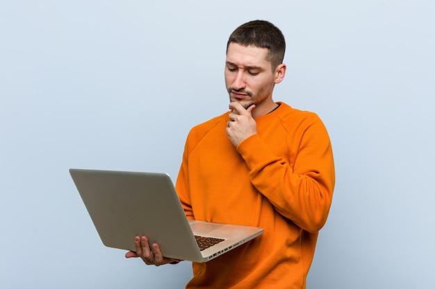 Junger kaukasischer mann, der einen laptop seitlich schaut mit zweifelhaftem und skeptischem ausdruck anhält.