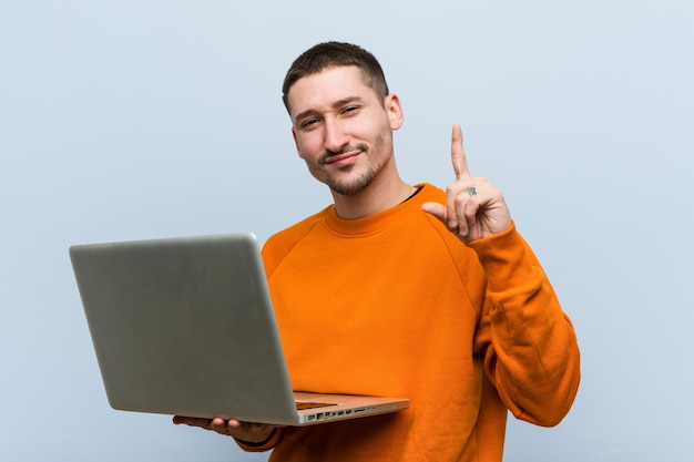 Junger kaukasischer mann, der einen laptop zeigt nummer eins mit dem finger hält.