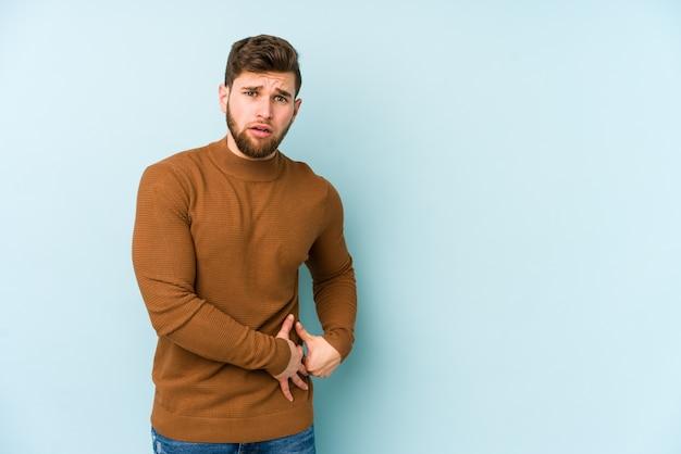 Junger kaukasischer mann, der einen leberschmerz, bauchschmerzen hat.