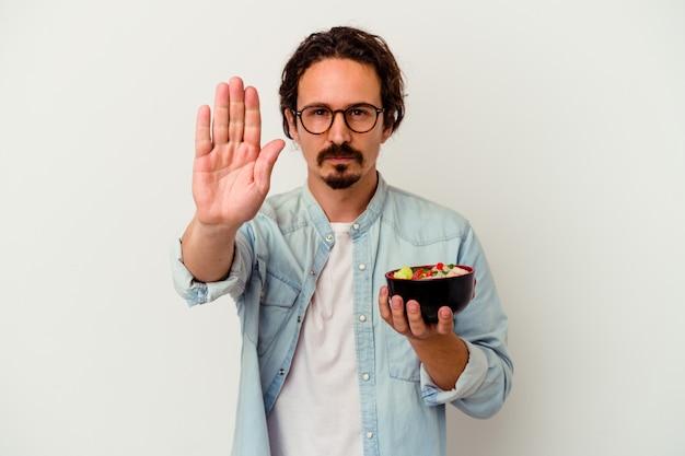 Junger kaukasischer mann, der einen ramen isst, der auf weißem hintergrund lokalisiert wird, der mit ausgestreckter hand steht, die stoppschild zeigt, das sie verhindert.