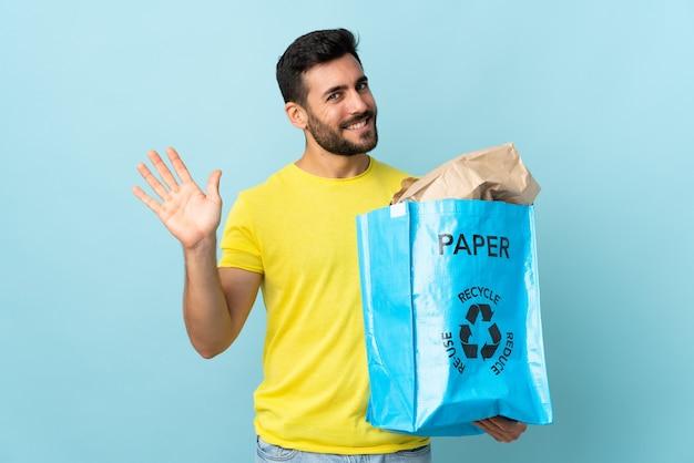 Junger kaukasischer mann, der einen recyclingbeutel lokalisiert auf blauer wand hält, die mit hand mit glücklichem ausdruck salutiert