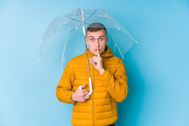 Junger kaukasischer mann, der einen regenschirm hält, der ein geheimnis hält oder um stille bittet.