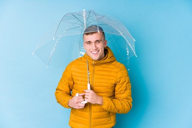 Junger kaukasischer mann, der einen regenschirm hält, der lacht und spaß hat.