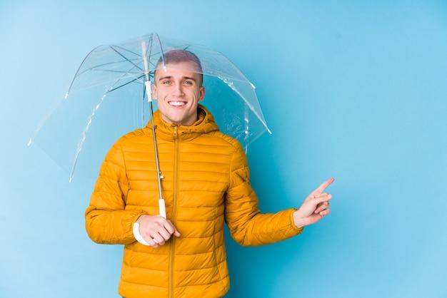 Junger kaukasischer mann, der einen regenschirm hält, der lächelt und beiseite zeigt und etwas an der leeren stelle zeigt.