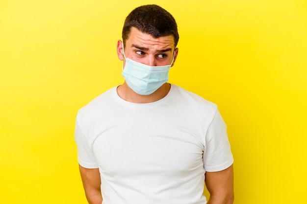 Junger kaukasischer mann, der einen schutz für coronavirus einzeln auf gelbem hintergrund trägt, verwirrt, fühlt sich zweifelhaft und unsicher.