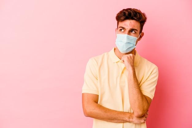 Junger kaukasischer mann, der einen schutz für coronavirus lokalisiert auf rosa hintergrund entspannte, entspannte das denken an etwas, das einen kopienraum ansieht.