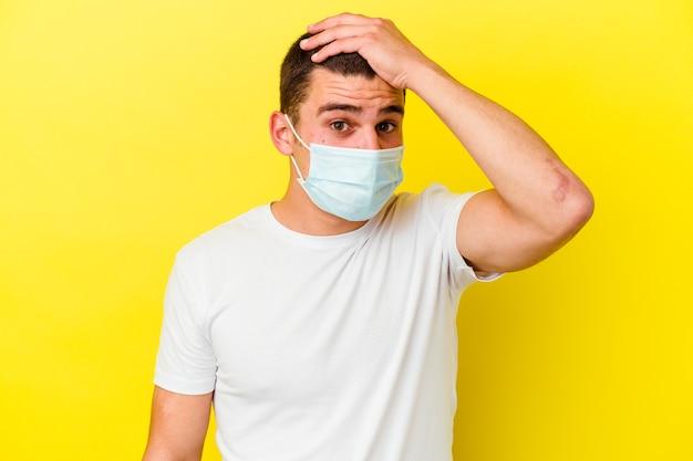 Junger kaukasischer mann, der einen schutz für coronavirus trägt, der auf gelber wand isoliert wird, die geschockt wird, sie hat sich an wichtiges treffen erinnert