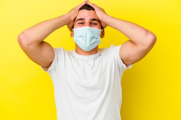 Junger kaukasischer mann, der einen schutz für coronavirus trägt, der auf gelber wand isoliert wird, lacht freudig und hält hände auf kopf. glückskonzept.