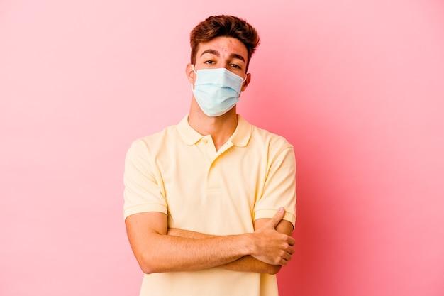 Junger kaukasischer mann, der einen schutz für coronavirus trägt, der auf rosa wand isoliert wird, der sich sicher fühlt und arme mit entschlossenheit kreuzt.