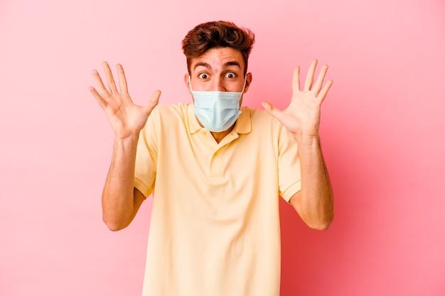 Junger kaukasischer mann, der einen schutz für coronavirus trägt, der auf rosa wand isoliert wird, die einen sieg oder erfolg feiert, er ist überrascht und schockiert