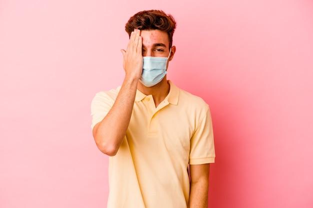 Junger kaukasischer mann, der einen schutz für coronavirus trägt, der auf rosa wand lokalisiert wird, die spaß hat, die hälfte des gesichts mit handfläche bedeckt.