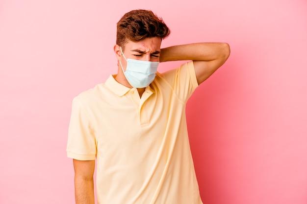 Junger kaukasischer mann, der einen schutz für coronavirus trägt, der auf rosafarbenem hintergrund isoliert ist und nackenschmerzen aufgrund einer sitzenden lebensweise hat.