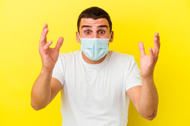 Junger kaukasischer mann, der einen schutz für coronavirus trägt, einzeln auf gelbem hintergrund, der eine angenehme überraschung empfängt, aufgeregt und die hände hebt.