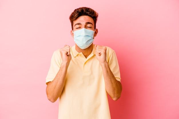 Junger kaukasischer mann, der einen schutz für coronavirus trägt, einzeln auf rosafarbenem hintergrund, der die faust hebt, sich glücklich und erfolgreich fühlt. sieg-konzept.
