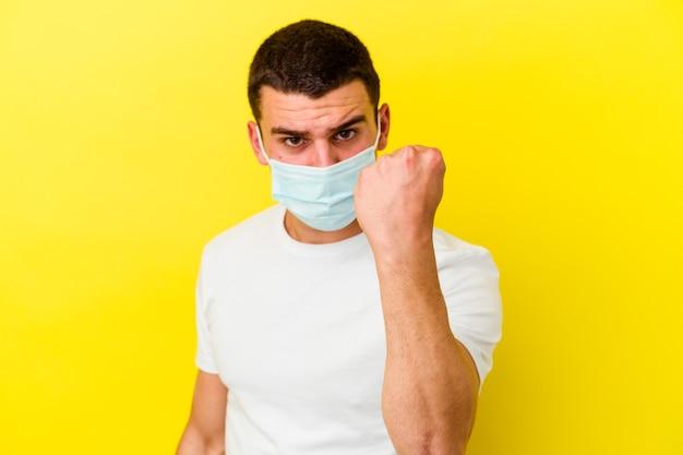 Junger kaukasischer mann, der einen schutz für coronavirus trägt, isoliert auf gelb mit faust, aggressivem gesichtsausdruck.