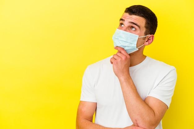Junger kaukasischer mann, der einen schutz für coronavirus trägt, isoliert auf gelbem hintergrund, der seitlich mit zweifelhaftem und skeptischem ausdruck schaut.