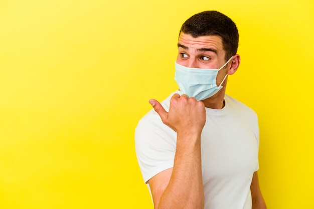 Junger kaukasischer mann, der einen schutz für coronavirus trägt, isoliert auf gelbem hintergrund, zeigt mit dem daumen weg, lacht und sorglos.