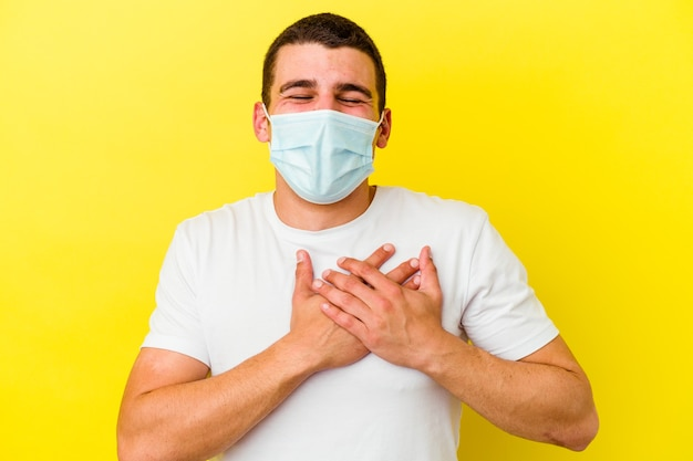 Junger kaukasischer mann, der einen schutz für coronavirus trägt, lokalisiert auf gelber wand, die lachend hände auf herz hält, konzept des glücks.
