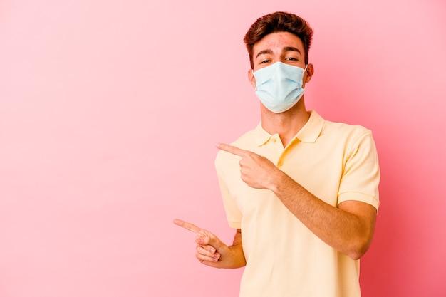 Junger kaukasischer mann, der einen schutz für coronavirus trägt, lokalisiert auf rosa wand aufgeregt zeigt mit zeigefingern weg
