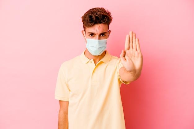 Junger kaukasischer mann, der einen schutz für coronavirus trägt, lokalisiert auf rosa wand, die mit ausgestreckter hand steht, die stoppschild zeigt, das sie verhindert.