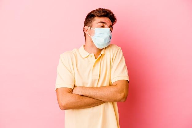 Junger kaukasischer mann, der einen schutz für coronavirus trägt, lokalisiert auf rosa wandumarmungen, sorglos lächelnd und glücklich.