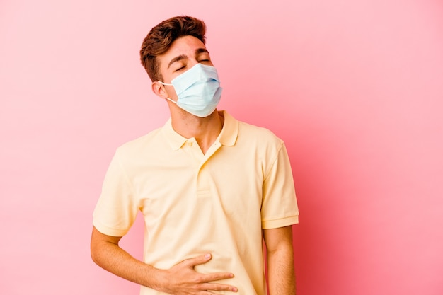 Junger kaukasischer mann, der einen schutz für das auf rosa wand isolierte coronavirus trägt, berührt bauch, lächelt sanft
