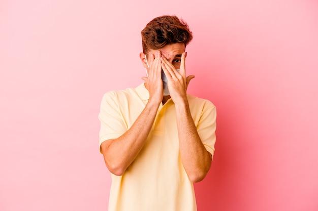 Junger kaukasischer mann, der einen schutz für das auf rosa wand isolierte coronavirus trägt, blinzelt durch erschrockene und nervöse finger.