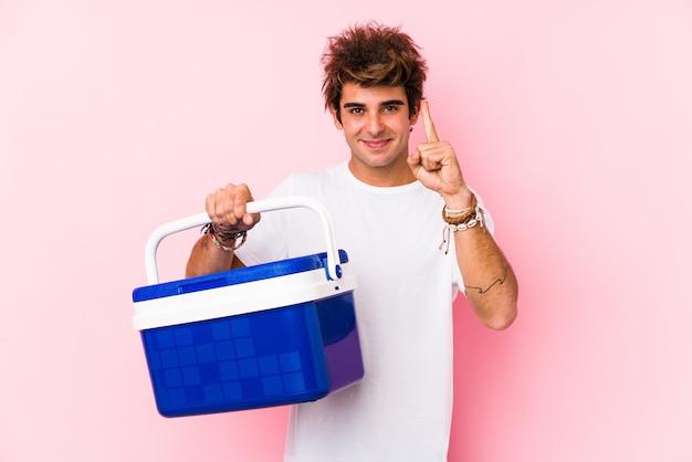 Junger kaukasischer mann, der einen tragbaren kühlschrank hält, der nummer eins mit finger zeigt.