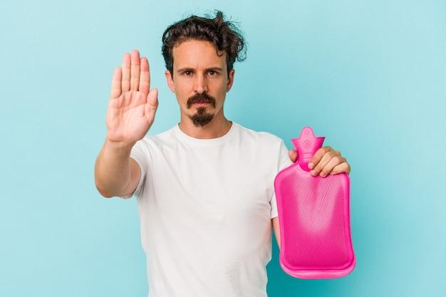Junger kaukasischer mann, der einen wassersack isoliert auf blauem hintergrund hält, der mit ausgestreckter hand steht und ein stoppschild zeigt und sie verhindert.
