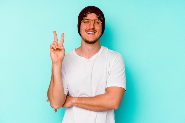 Junger kaukasischer mann, der einen wollhut trägt, der auf blauem hintergrund isoliert ist und nummer zwei mit den fingern zeigt.