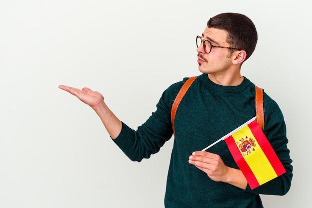 Junger kaukasischer mann, der englisch isoliert auf weiß lernt, der einen kopienraum auf einer handfläche zeigt und eine andere hand auf der taille hält.