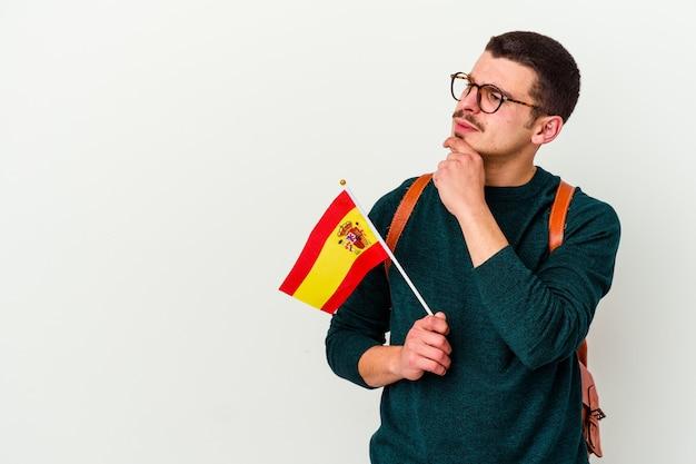 Junger kaukasischer mann, der englisch studiert, isoliert auf weißer wand, die seitwärts mit zweifelhaftem und skeptischem ausdruck schaut.