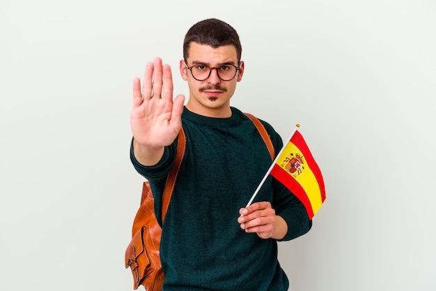 Junger kaukasischer mann, der englisch studiert, lokalisiert auf weißem hintergrund stehend mit ausgestreckter hand, die stoppschild zeigt, das sie verhindert.
