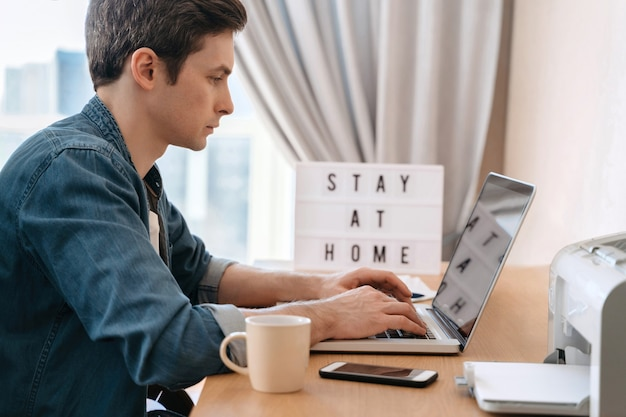 Junger kaukasischer mann, der entfernt mit laptop und smartphone in seinem zimmer arbeitet