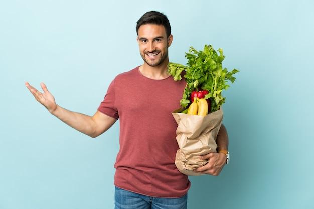 Junger kaukasischer mann, der etwas gemüse kauft, das auf blauer wand isoliert wird, die hände zur seite für einladung zum kommen ausdehnt