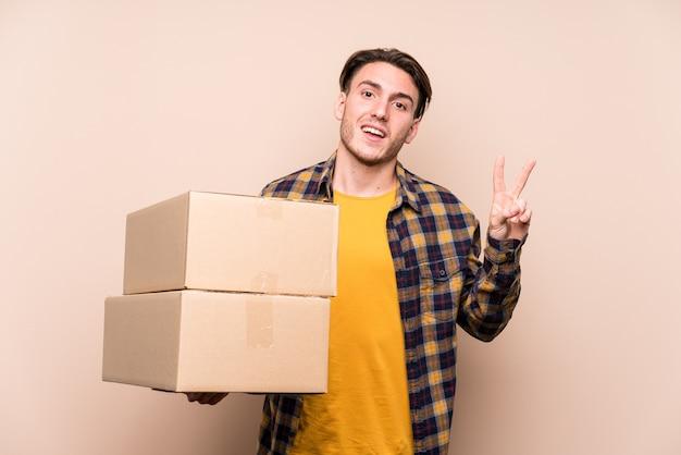 Junger kaukasischer mann, der freudige und sorglose kisten hält, die ein friedenssymbol mit den fingern zeigen.