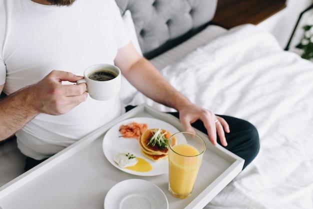 Junger kaukasischer mann, der gesundes frühstück im bett auf tablett isst
