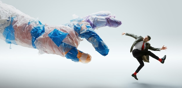 Junger kaukasischer mann, der große plastikhand auf weißer wand vermeidet. männliches model in bürokleidung kämpft in bewegung und action. sieht wütend, verängstigt, unter druck aus. öko-probleme, umweltverschmutzung, recycling.
