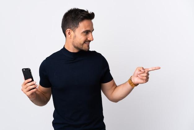 Junger kaukasischer mann, der handy verwendet auf lokalisiertem weiß zeigt auf die seite, um ein produkt zu präsentieren