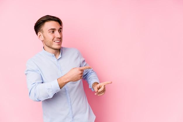 Junger kaukasischer mann, der in einem rosa lokalisierten aufgeregten zeigen mit zeigefingern weg aufwirft.
