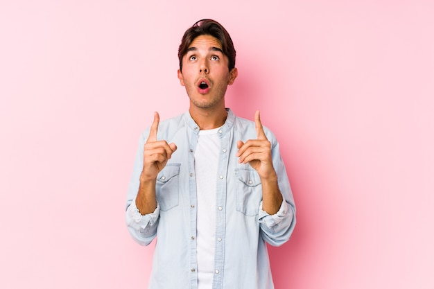 Junger kaukasischer mann, der in einer rosa wand lokalisiert zeigt, die oben mit geöffnetem mund zeigt.