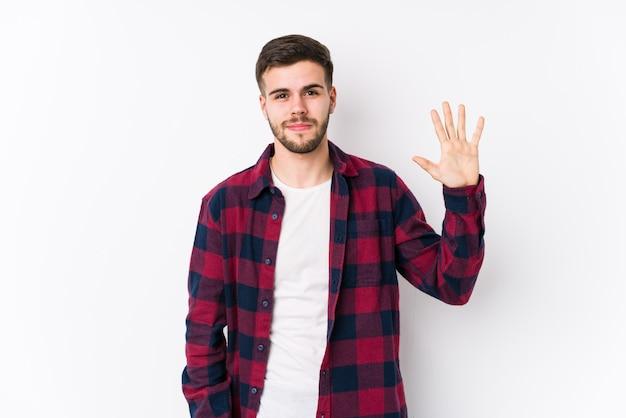 Junger kaukasischer mann, der in einer weißen wand isoliert lächelnd fröhlich zeigt, zeigt nummer fünf mit den fingern.