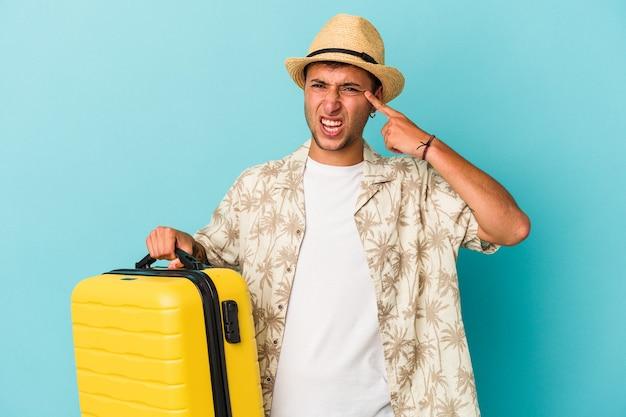 Junger kaukasischer mann, der isoliert auf blauem hintergrund reisen wird und eine enttäuschungsgeste mit dem zeigefinger zeigt.