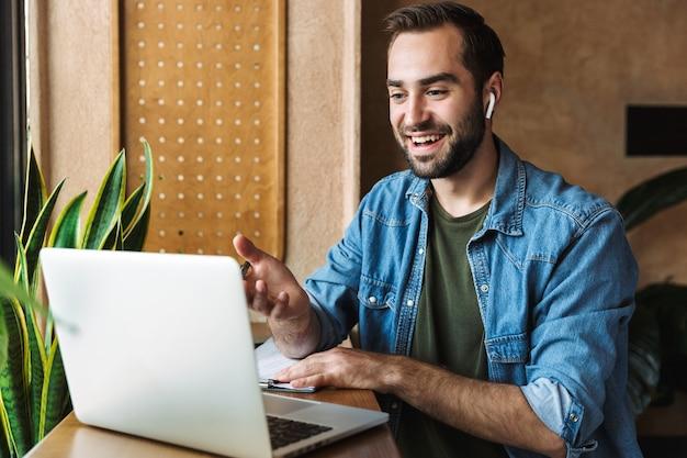 Junger kaukasischer mann, der jeanshemd mit ohrstöpsel und laptop trägt, während er im café drinnen arbeitet?