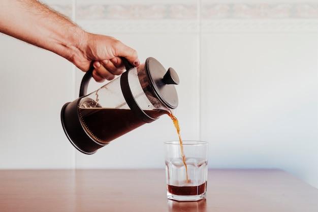 Junger kaukasischer mann, der kaffee in einem glas dient